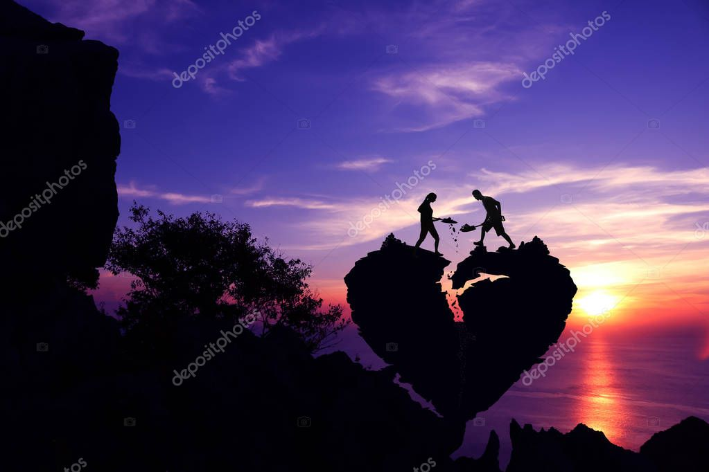 Valentine day,Silhouette Couple helping to shoveling stone for repair the broken heart shape rock on the mountain.