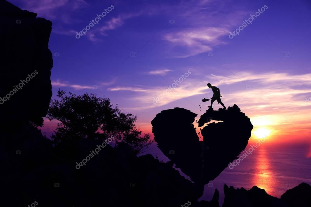 Valentine day concept, Man shoveling stone to repair the broken heart shape rock on the mountain.