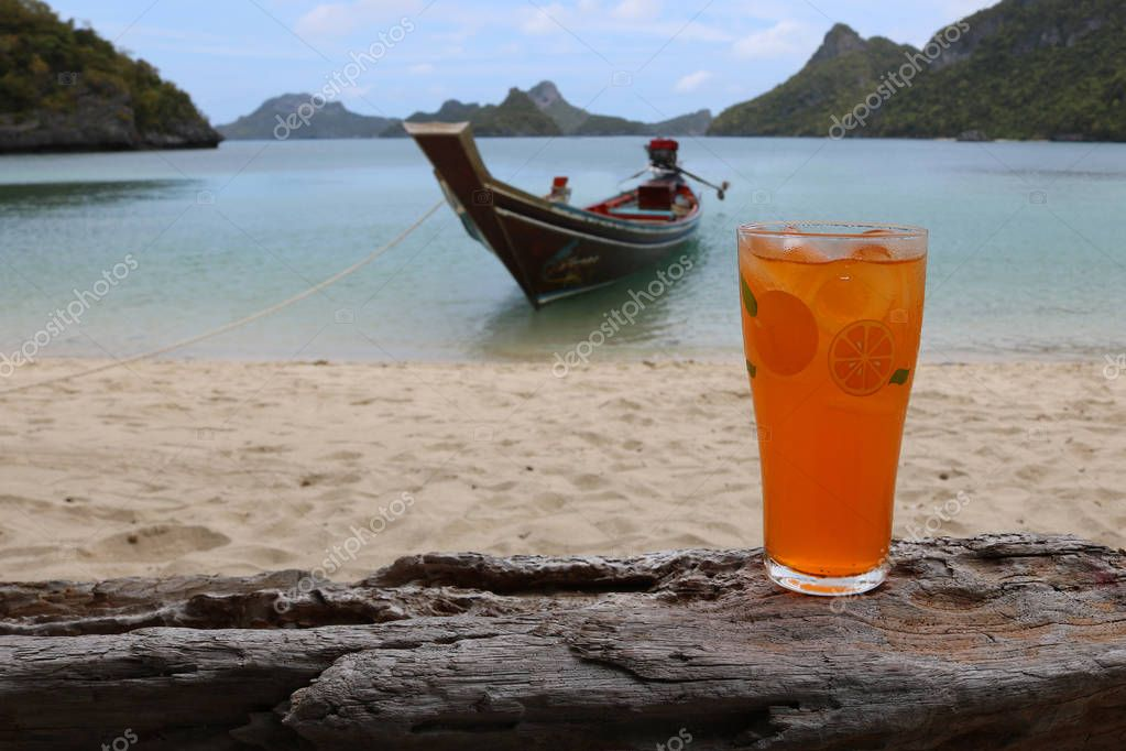 Glass of orange juice on the beach with views of the archipelago Islands .