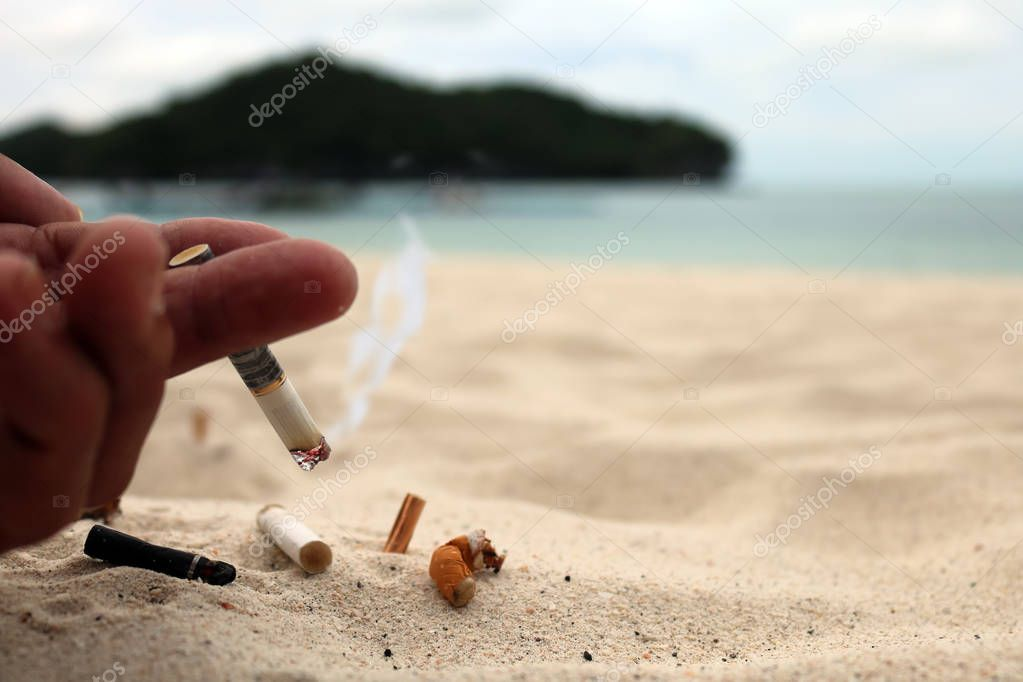 Hand smoking cigarette and ashtray on the beach