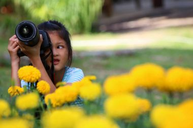 Asian girl learning to use dslr camera in the garden