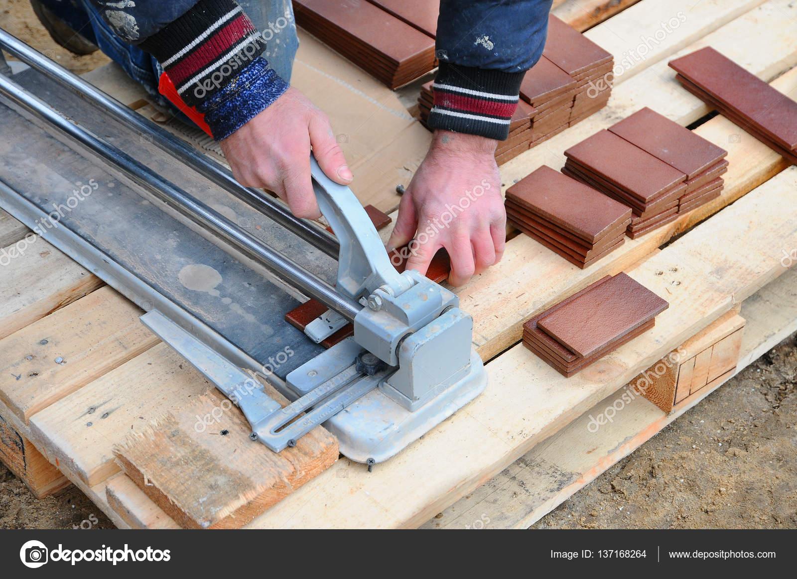 Operaio edile piastrellista taglia piastrelle piastrelle. lavorando