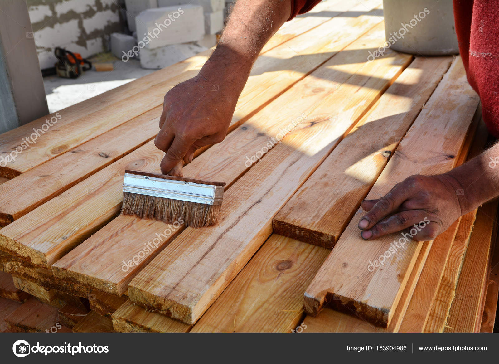 Bauarbeiter arbeitet mit Holzbalken. Die Arbeitskraft Bürsten die ...