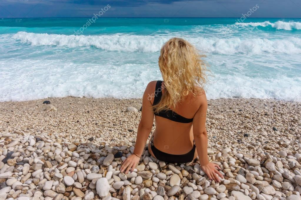 rear view of blonde girl sitting on a Caribbean beach