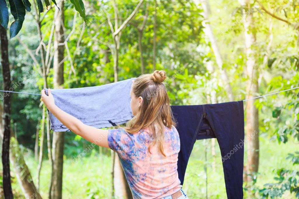 young white girl hanging out the clothes to dry after washing