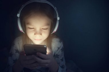 Little girl in headphones with phone at night
