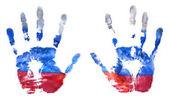 Fotografia Limpronta delle mani dei colori della bandiera russa, gouache. La bandiera della Federazione Russa