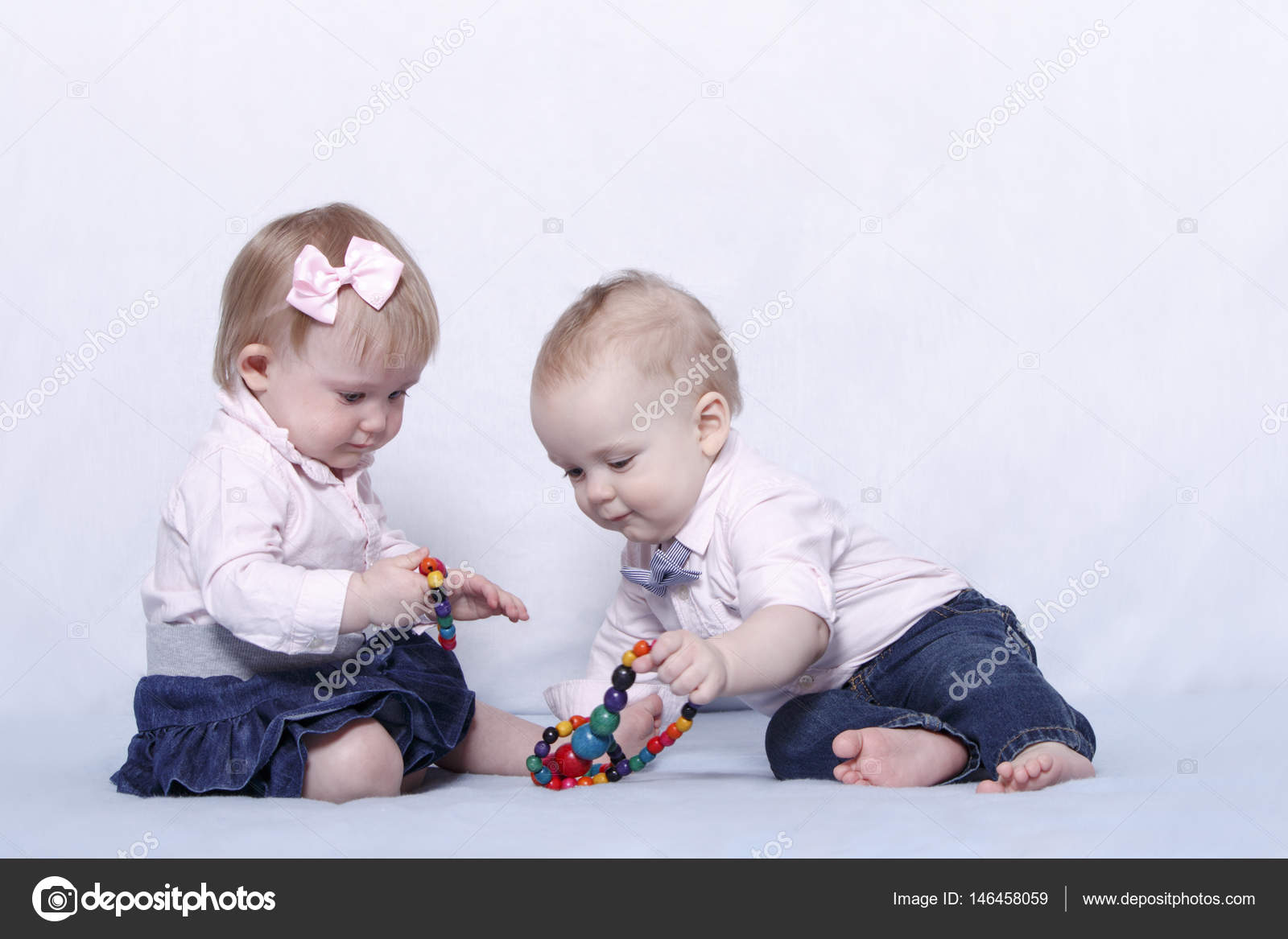 love story of two cute kids. infant baby girl and boy playing with