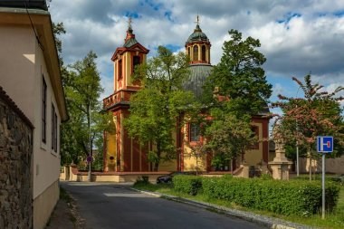 Kunratice, Prague / Czech Republic - May 6 2020: The baroque church of St James the Great with red and yellow facade surrounded with green trees. Sunny day with blue sky and white clouds.