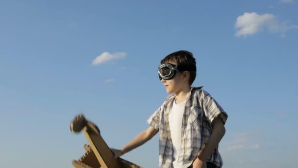 Egy kisfiú, aki kartonpapírral játszik a parkban napközben. A boldog játék fogalma. A gyerek jól érzi magát a szabadban. A kék ég hátterén készült kép.