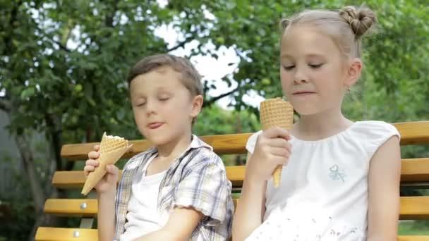 Dvě šťastné děti jedí zmrzlinu v parku ve dne. Koncepce zdravého jídla.