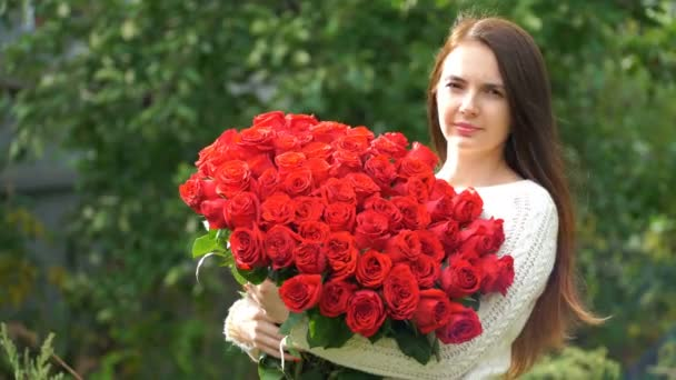 footage woman holding a bouquet of roses outdoors. 4k