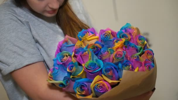 young woman is smelling bouquet of rainbow roses