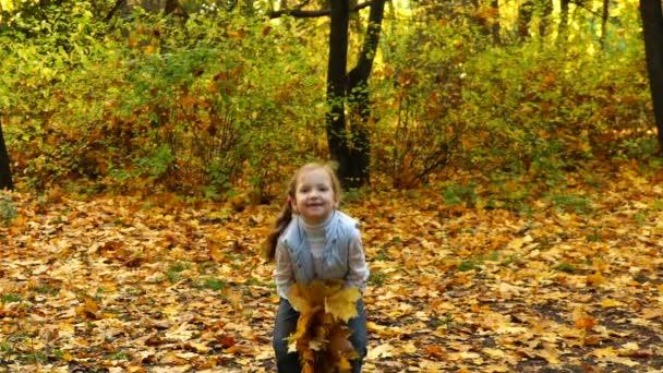 Mädchen wirft Herbstlaub in den Park. hd video.