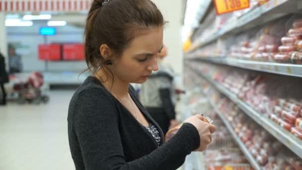 Záběry žena koupí párky v supermarketu. 4k video.