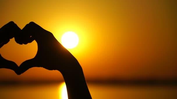 Frau macht Herz und Hände dirigiert den Sonnenuntergang