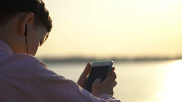 mladý muž používá aplikace na smartphone nebo šplhá v sociálních sítích.