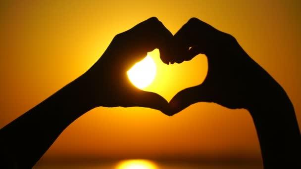 Žena dělá srdce a ruce směřuje na západ slunce