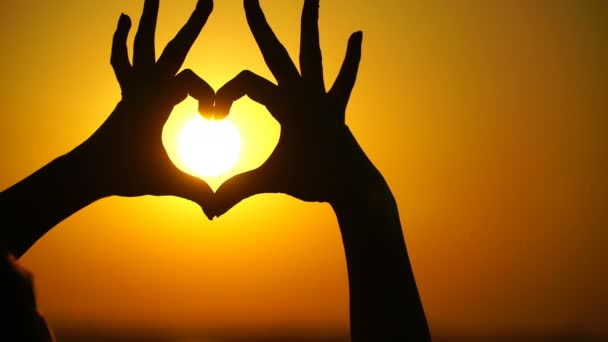 Woman makes heart and hands directs the sunset