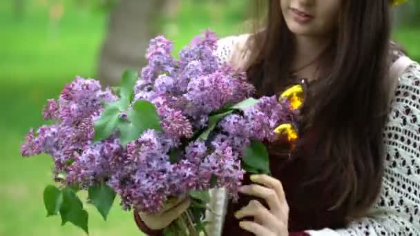 Woman holding a bouquet of lilacs in blossom.