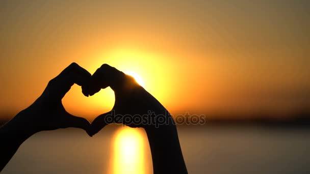 Nő teszi szív és kéz irányítja a naplemente