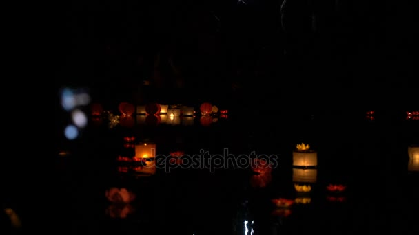 People run water lanterns at night.