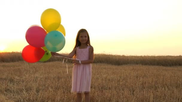 girl walking in a field with balloons