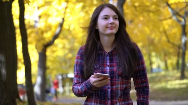 Mädchen geht im Herbst im Park spazieren und nutzt die Anwendung auf ihrem Smartphone