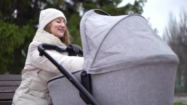 Young mother with newborn child outdoor. She sitting on the bench with baby sleeping in pram