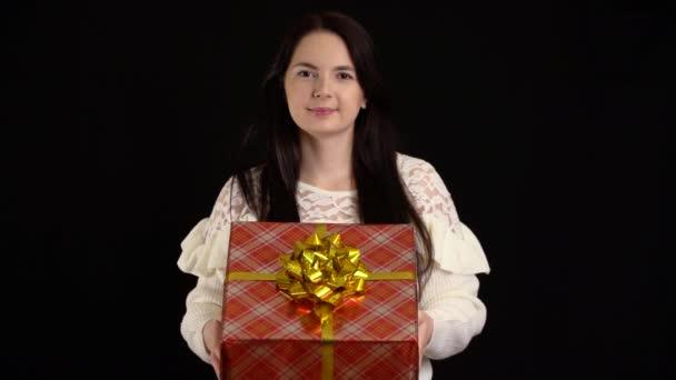 Mladá žena s dárkovou krabicí na černém pozadí. dárková krabička s bílou stuhou na Šťastný Nový rok, Veselé Vánoce, Valentýn, narozeniny.