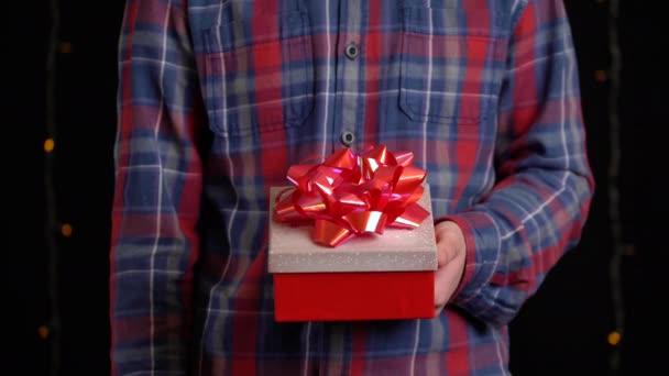chlapec s dárkovou krabicí na černém pozadí. dárková krabička se stuhou na Šťastný Nový rok, Veselé Vánoce, Valentýn, narozeniny