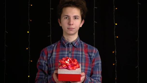 egy fekete hátterű ajándékdobozos fiú. ajándék doboz szalaggal Boldog új évet, Boldog karácsonyt, Valentin-napot, születésnapot