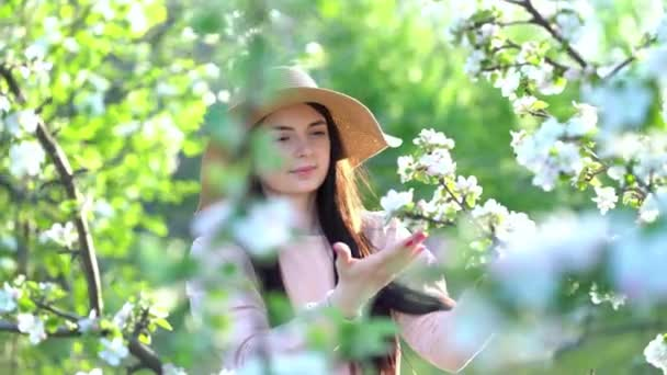 Beauty young woman enjoying apple blooming spring orchard.
