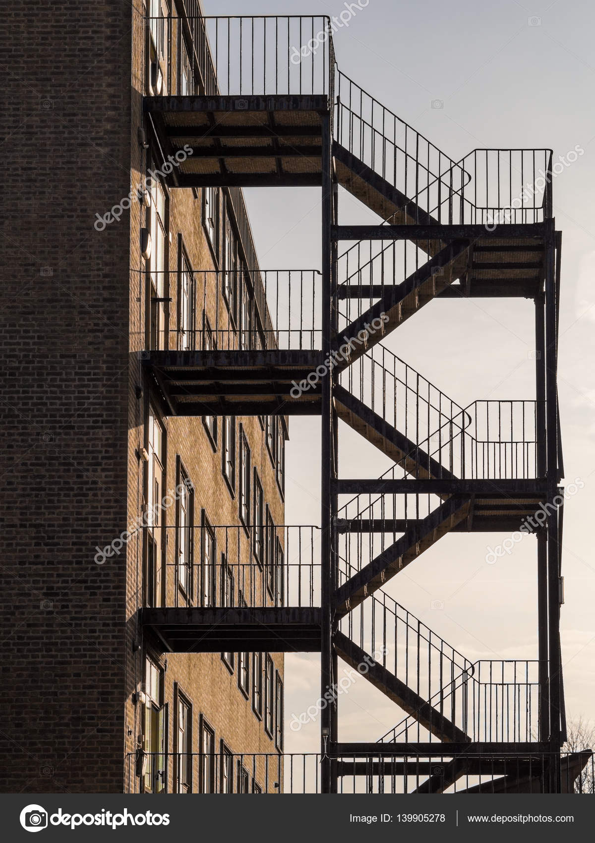External Fire Escape Silhouette. Fire Escape Is Iron With Five Flights Of  Steps And Handrails. Building Is Generic Square Office Style Building In  Brick.