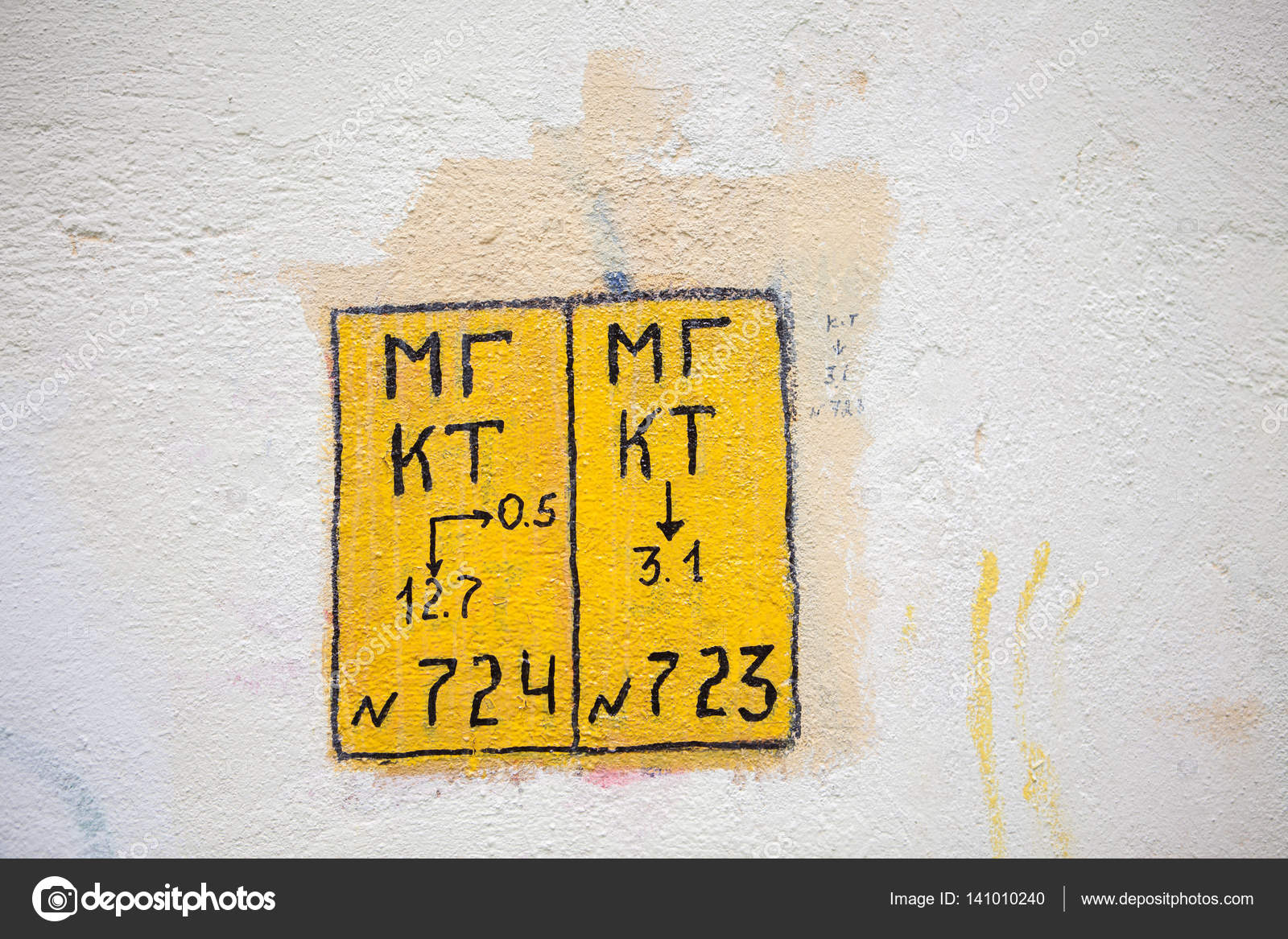 Yellow square technical mark on the wall with numbers and cyrillic ...