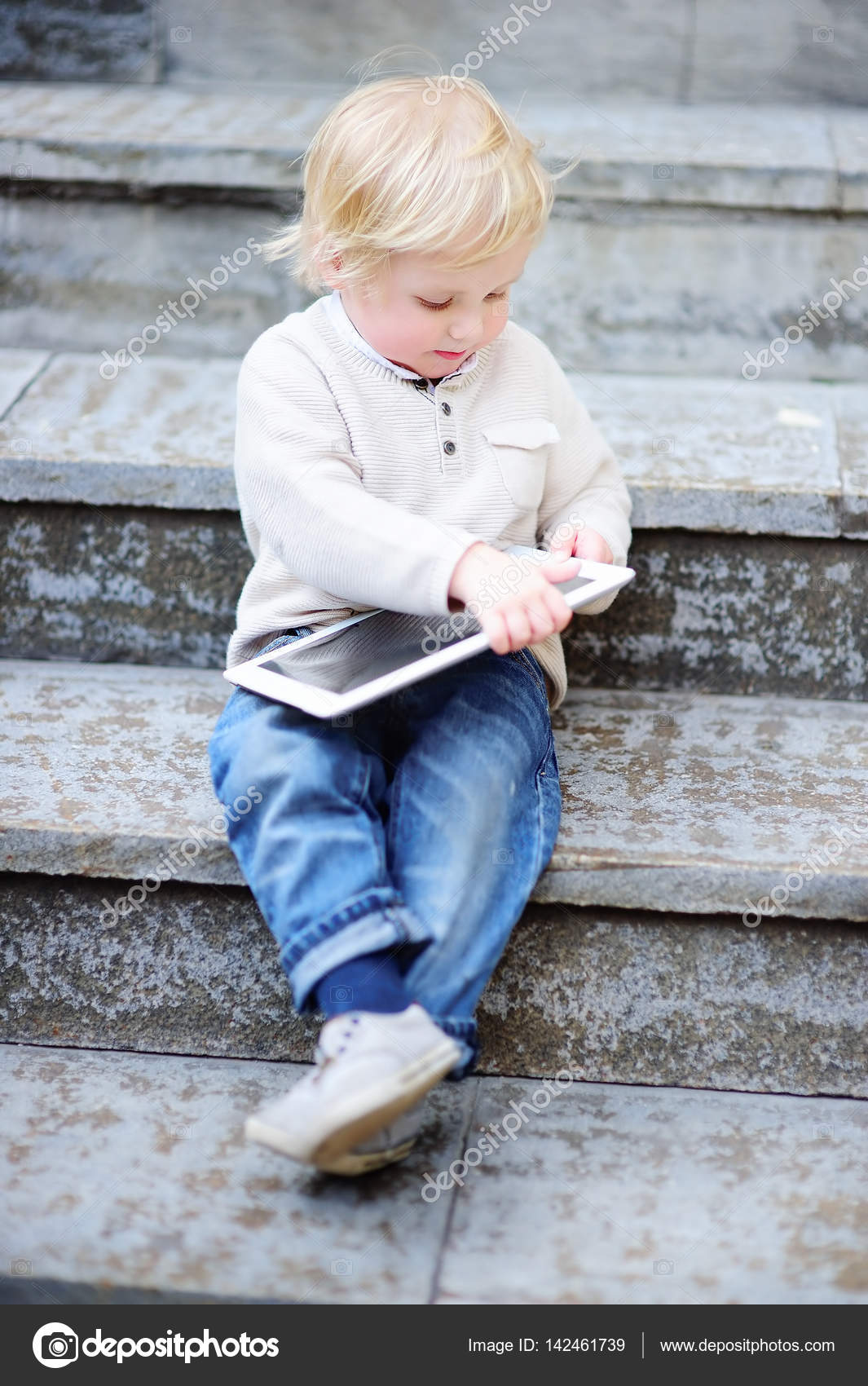 fdb42efb2ed0 Cute blonde toddler boy playing with a digital tablet outdoors– stock image
