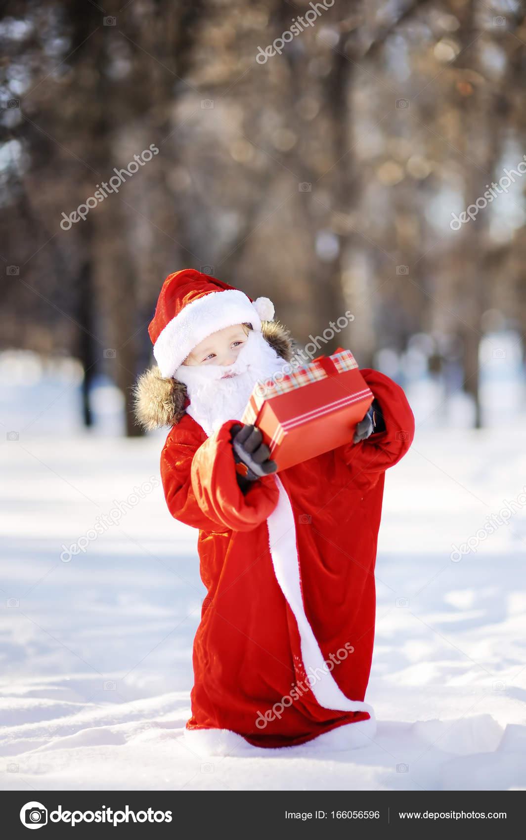 Lustige kleine Junge gekleidet wie Santa Claus mit roten Kasten mit ...