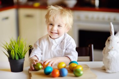 Cute toddler child hunting for easter egg on Easter day