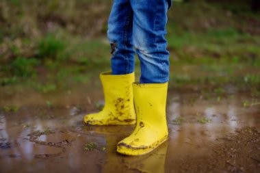 Mischievous preschooler child wearing yellow rubber rain boots jumping in large wet mud puddle. Kid playing and having fun. Outdoors games for children.