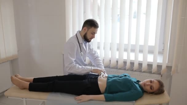 Doktor palpates břicho mladé dívky