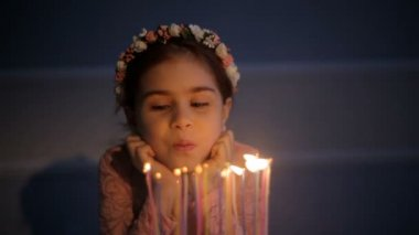 Closeup of a young girl blowing out birthday candles