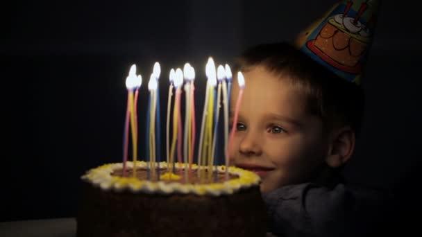 Childrens birthday. Children near a birthday cake with candles.