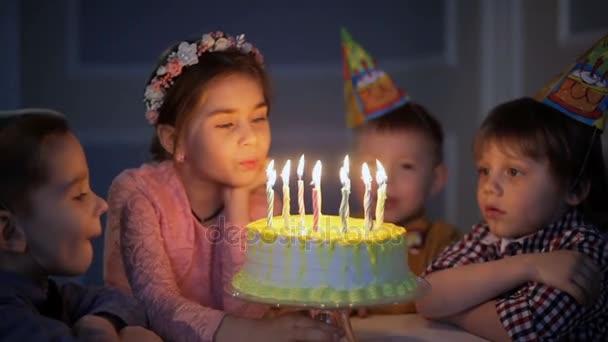 Gyerekek ünneplő születésnapi partiján, és fúj gyertyák, a torta