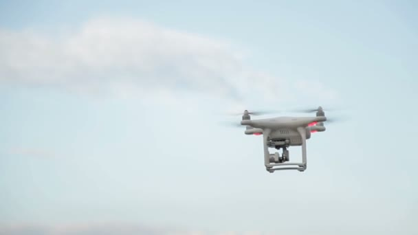 White drone quadcopter flying in the blue sky