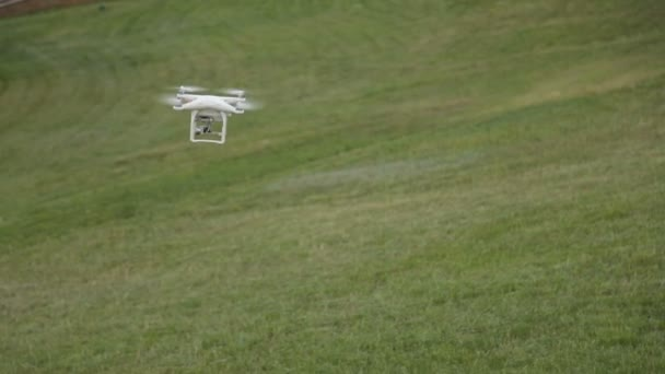 White drone quadcopter flying in the blue sky on the background of the grass