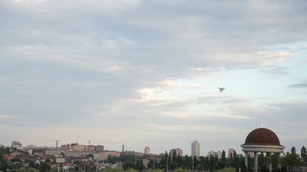 White drone quadcopter flying in the blue sky on the background of the city