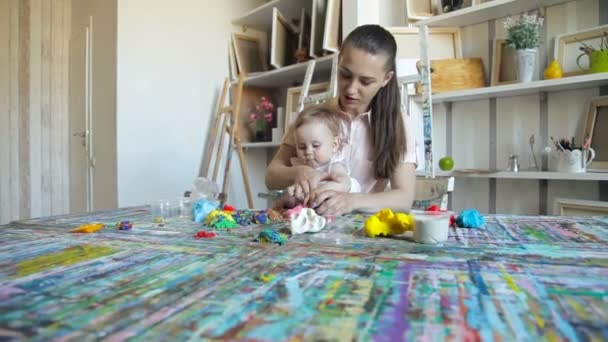 kid girl and mom play with plasticine in the art studio. Educational game