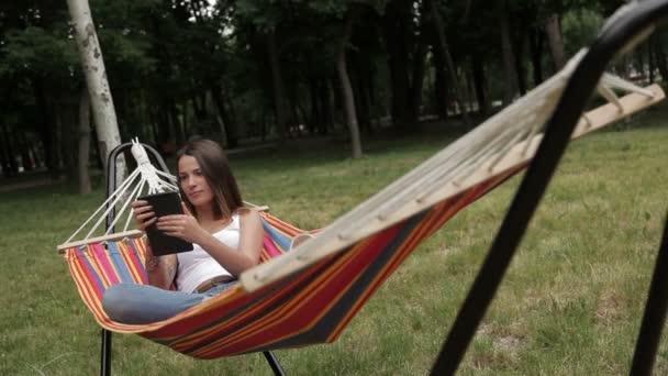 dívka odpočívá v houpací síti s tabletem v ruce na pozadí lesa