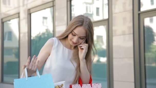 Mädchen mit glücklichem Lächeln hält viele Einkaufstüten in der Hand und telefoniert