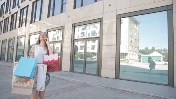 Dívka se šťastným úsměvem drží mnoho nákupní tašky, mluvil po telefonu